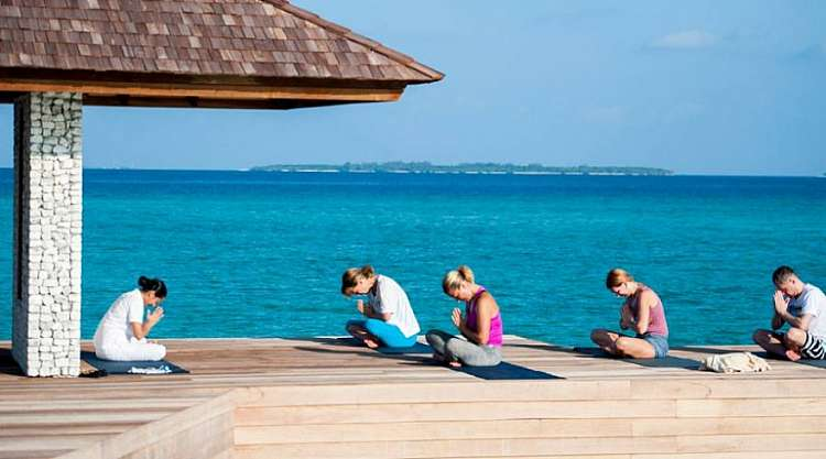 Yoga e massaggi ayurvedici su una spiaggia da sogno di un atollo